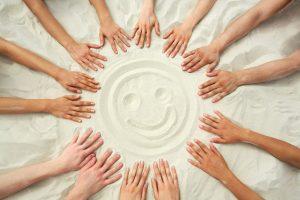 Hands Encircle A Face Drawn In Beach Sand