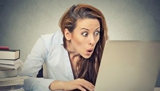 Woman Looks Surprised And Stares At Computer