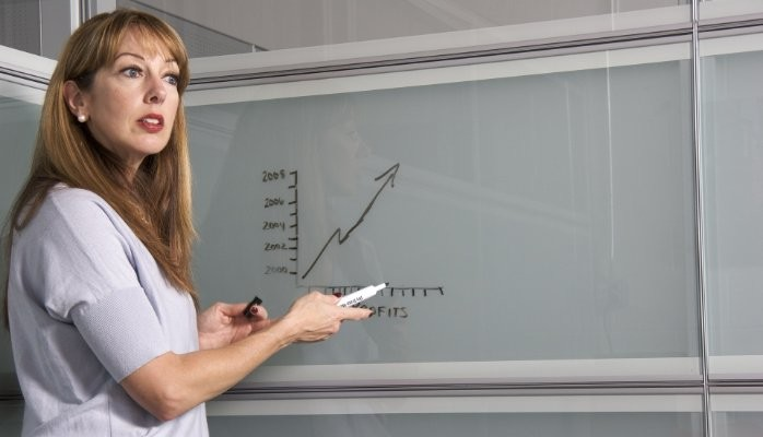 Woman Presentor In Front Of White Board With Chart